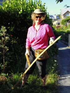 Amanda, scything long grass in the orchard for compost and mulch.