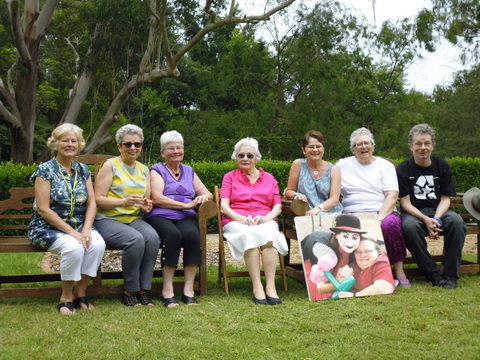 Pat at her 90th birthday party, with children Deborah, Adrienne, Charmaine, Barbara, Chris Ann, Jess , and, in front, a painting of Patience (and clown friend) not long before her death last year.